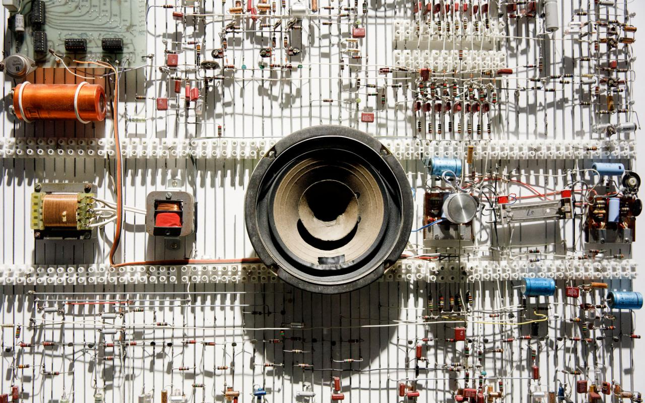 Helle Platte mit Lautsprecher und verschiedenen Bauteilen