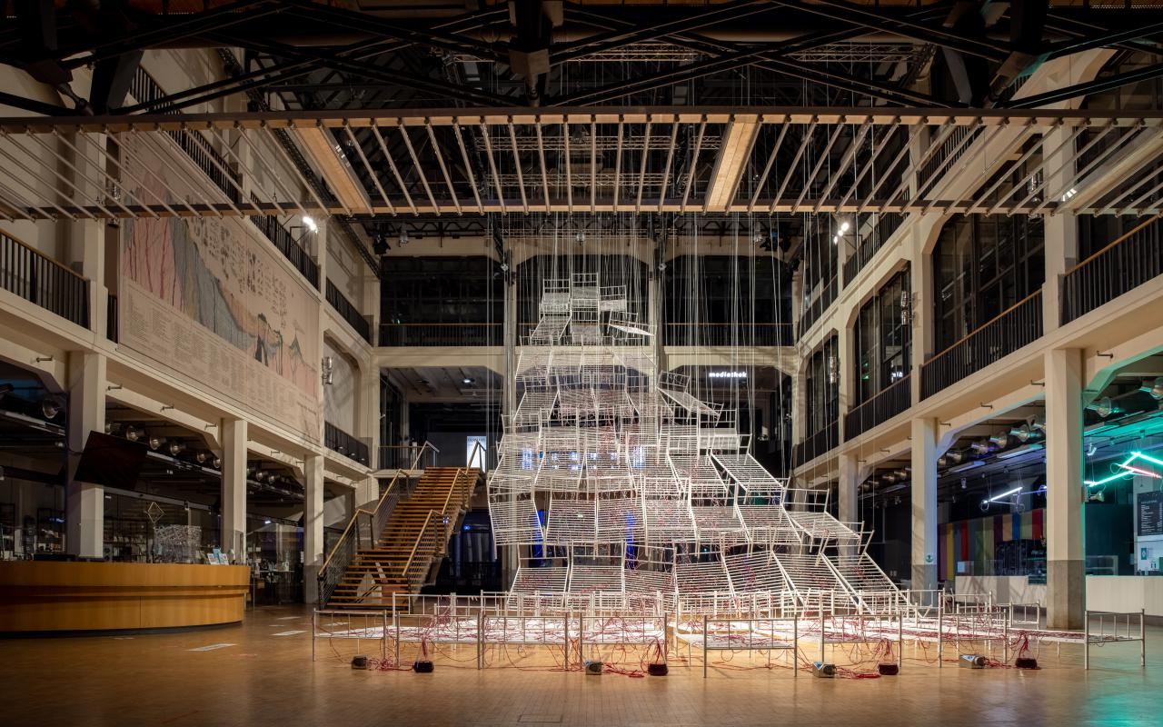"""Installation view of Chiharu Shiota`s work """"Connected to Life"""". You can see bedsteads lined up and connected to each other, crisscrossed by red tubes that rise further and further from the floor and together form a kind of pathway upwards."""
