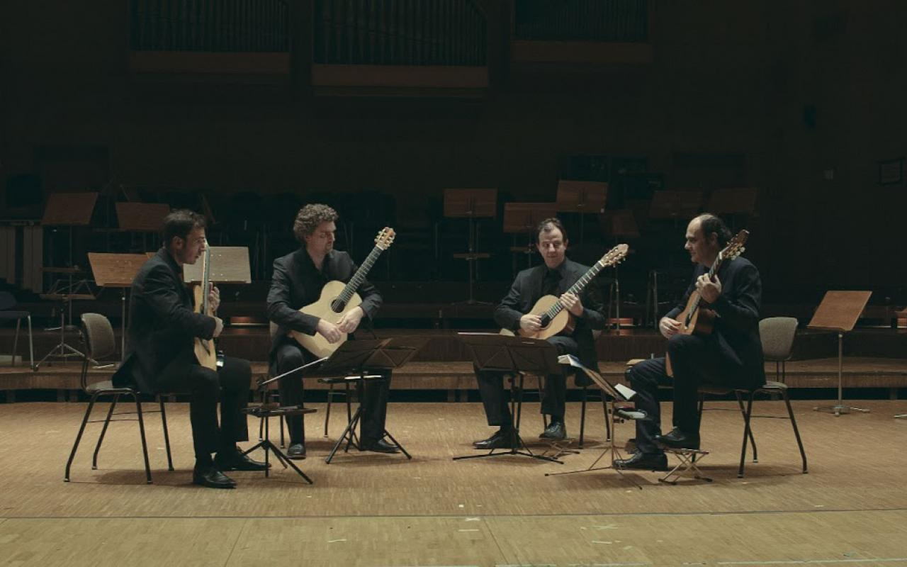 Four men are sitting in an open circle with guitars in their hands.