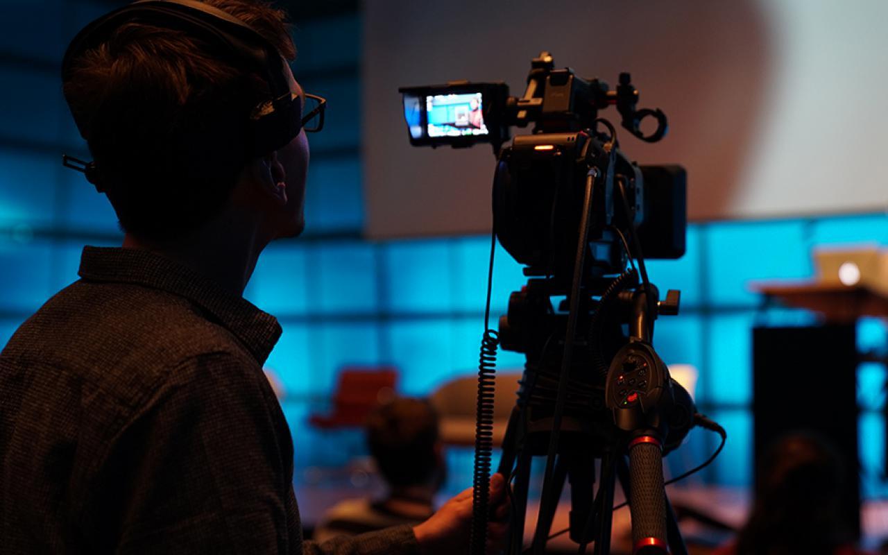 Ein Kameramann blick in das Display einer Kamera.