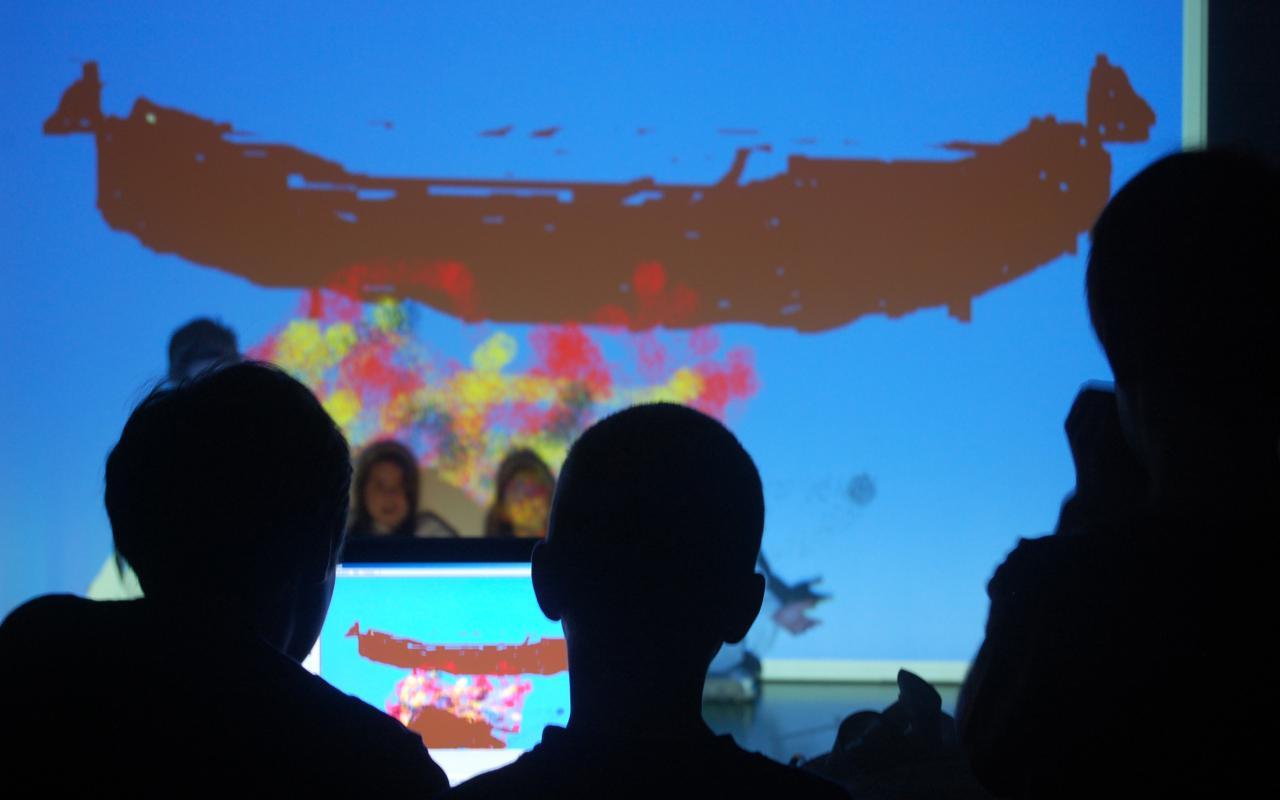Kinder sitzten vor dem Computer und bearbeiten ein Bild, das mit dem Beamer auf eine Leinwand und die Anzüge der Kinder davor geworfen wird. Sie sitzen unter einer großen Wurst.