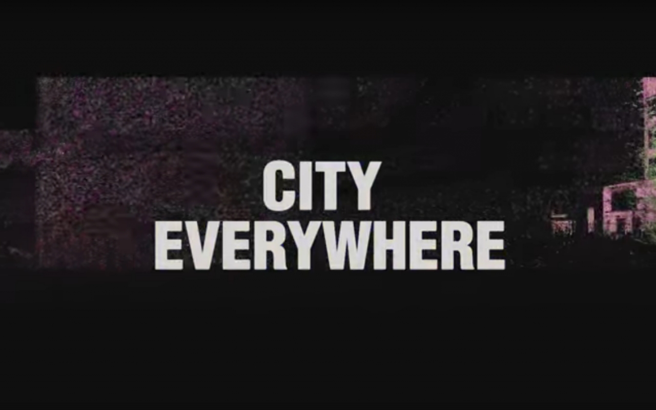 """The lettering """"City Everywhere"""" against a black background with an industrial building."""