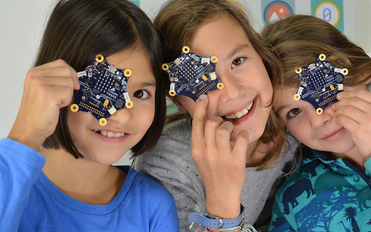 Foto von drei jungen Mädchen, die je eine Calliope mini Platine vor ihr Gesicht halten.