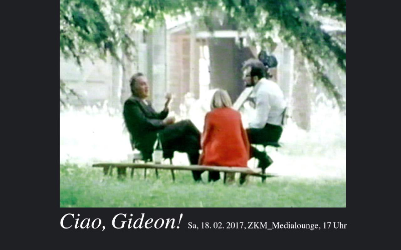Two men and a woman sitting in a meadow under a tree. One man holds a camera in his hand.