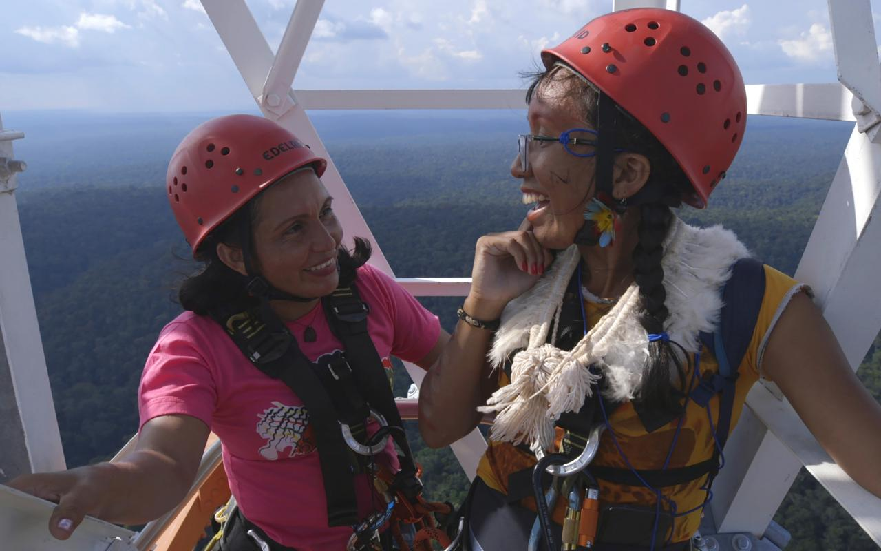 Zu sehen sind zwei Frauen, die weit oben auf einem Turm stehen. Sie tragen Sicherheitshelme und lachen. Im Hintergrund sieht man bis zum Horizont Wald.