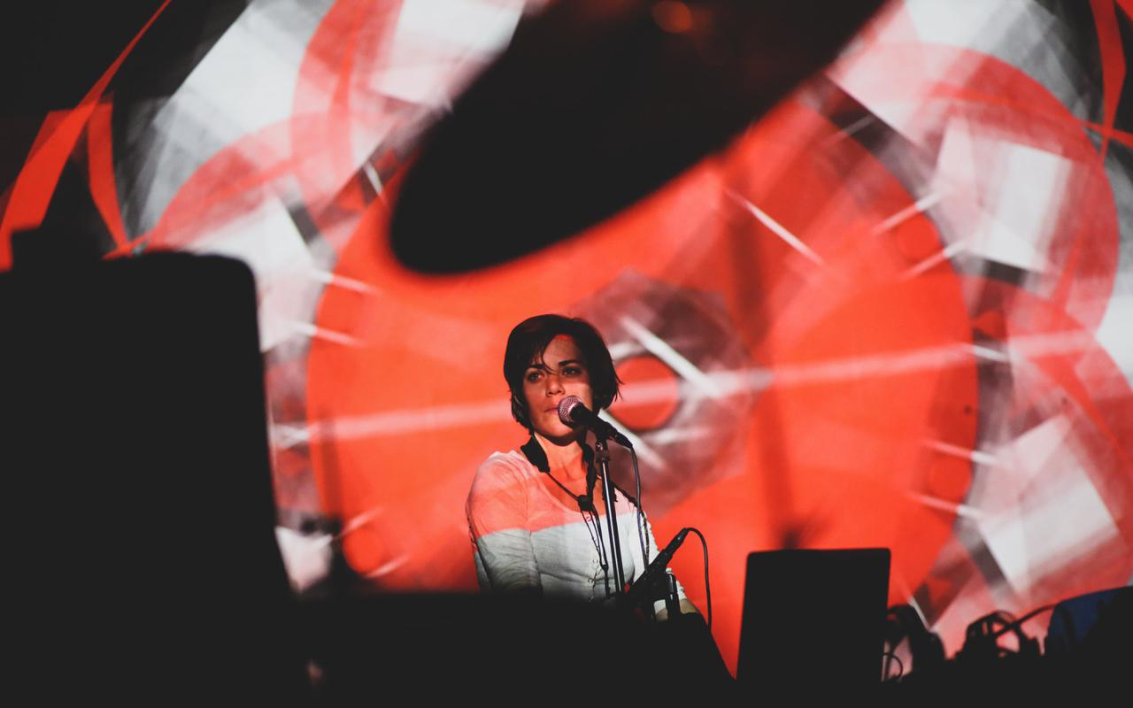 A woman at the microphone, in front of her red-white light projections.