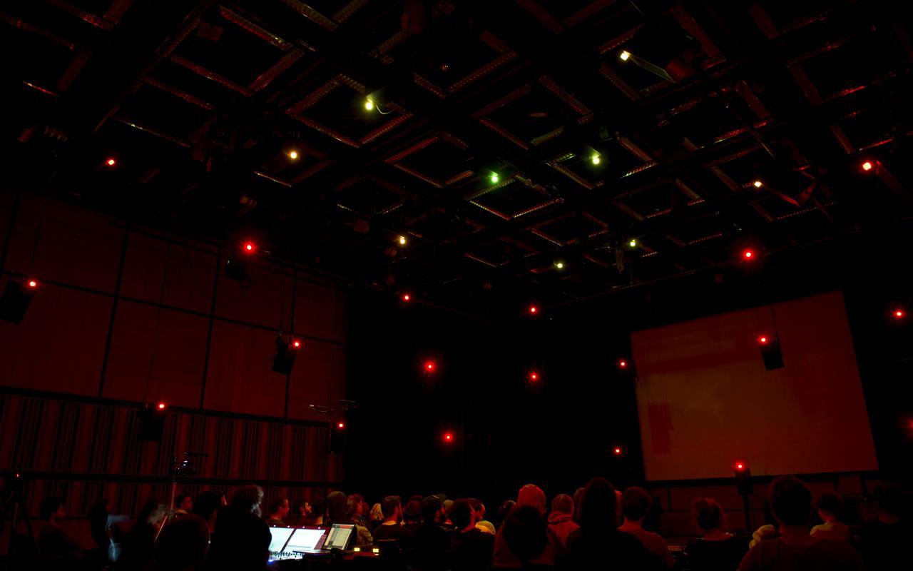 Ein dunkler großer Raum mit vielen sitzenden Menschen. An der Decke sind einzelne Lichter zu sehen.