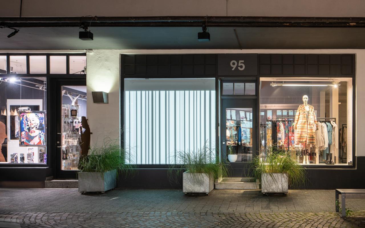 Zu sehen ist eine riesige leuchtende Leinwand inmitten der Stadt Karlsruhe, mit wechselnden vertikalen Schatten- und Lichtspuren.