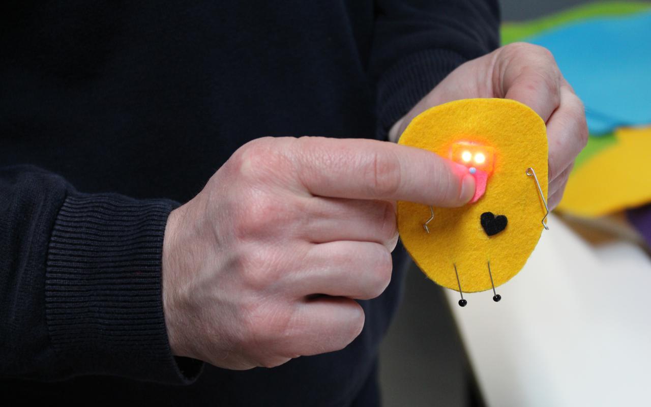 Jemand hält ein kleines textiles Kunstwerk in der Hand und drückt mit dem Finger darauf um eine LED zum leuchten zu bringen