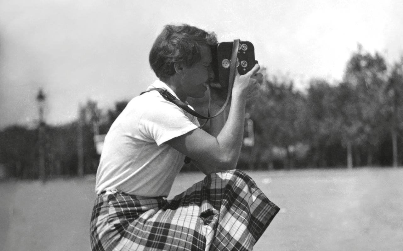 The black and white photograph shows a woman in squatting position with a camera.