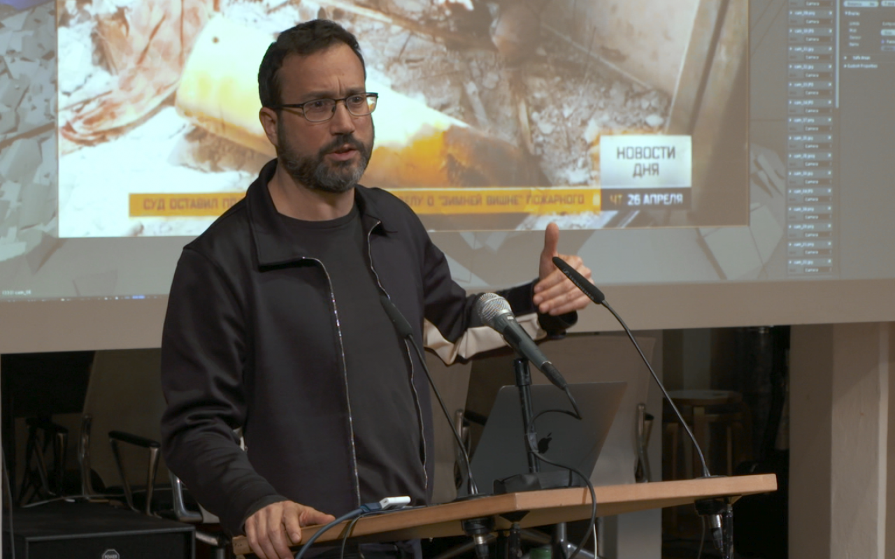 Eyal Weizman, a man with a beard and specs giving a lecture in front of a screen.