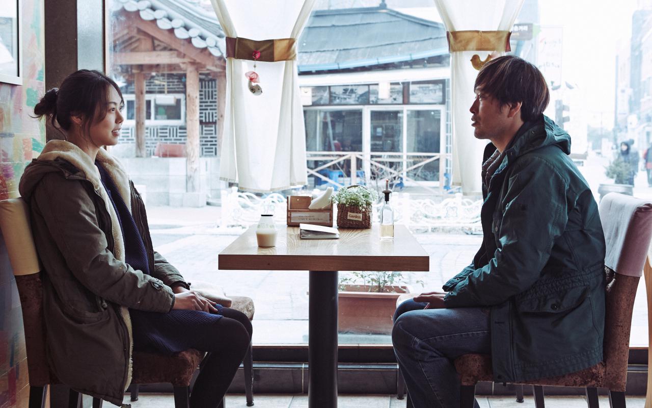 Ein Mann und eine Frau sitzen sich an einem Tisch gegenüber.