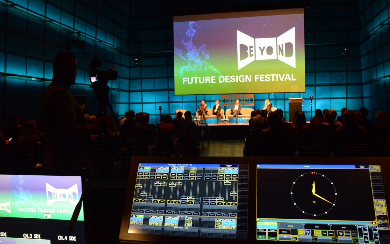 View into a large darkened room. On the opposite wall is a large screen with the logo of the Beyond Future Design Festival.