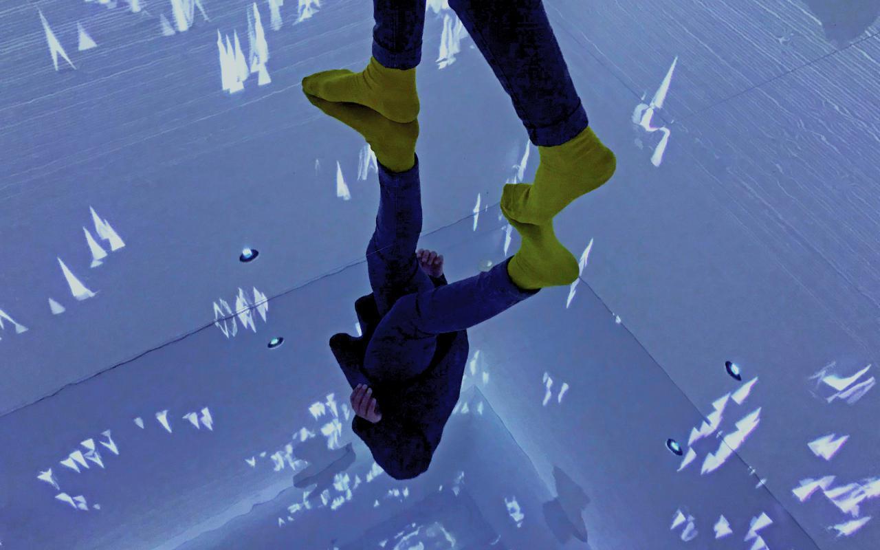 Feet in yellow socks mirrored on a mirrored floor panel