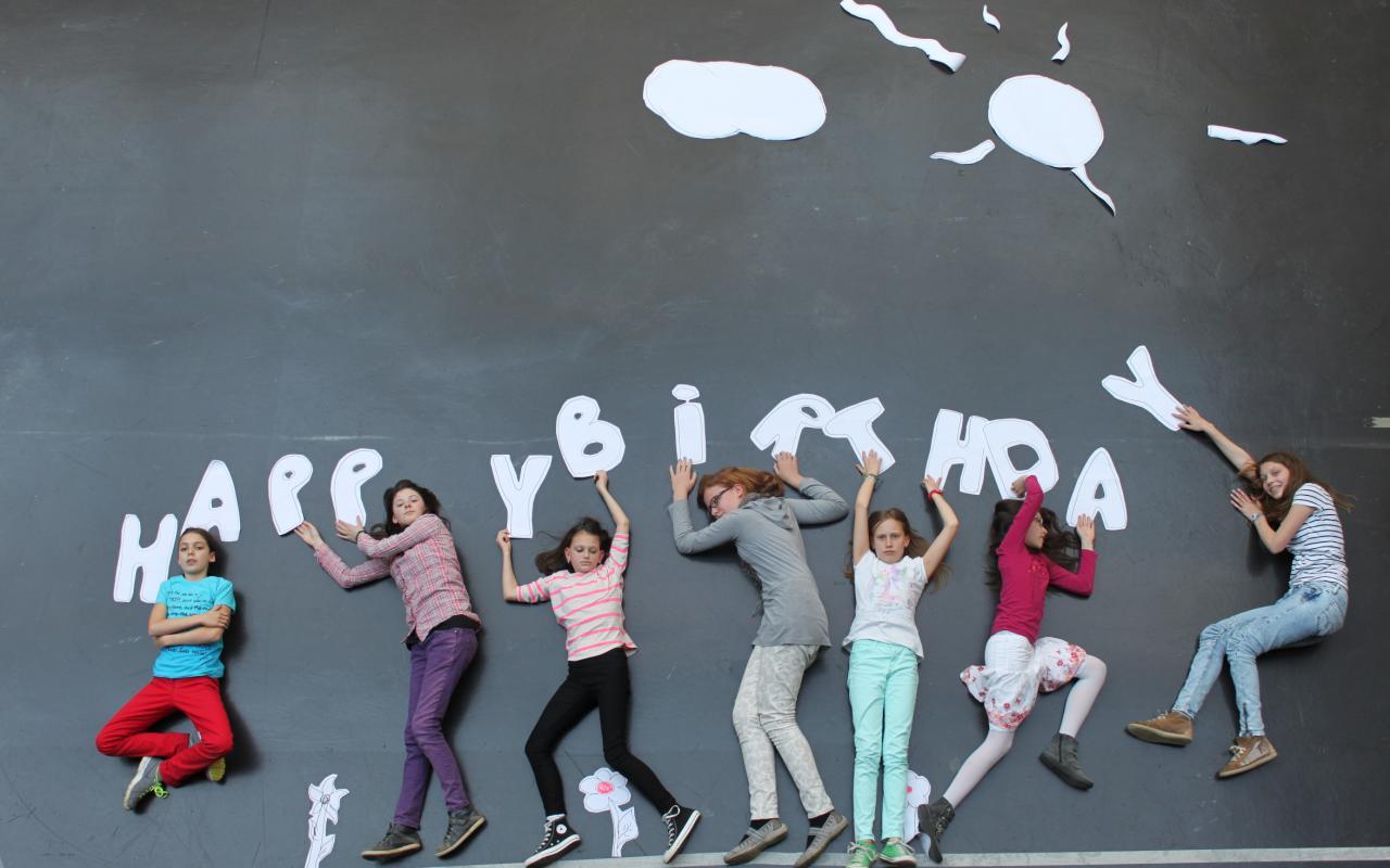 Kinder halte, auf dem Boden liegend, verschiedene Buchstaben aus Papier hoch. Zusammen ergeben sie »Happy Birthday«