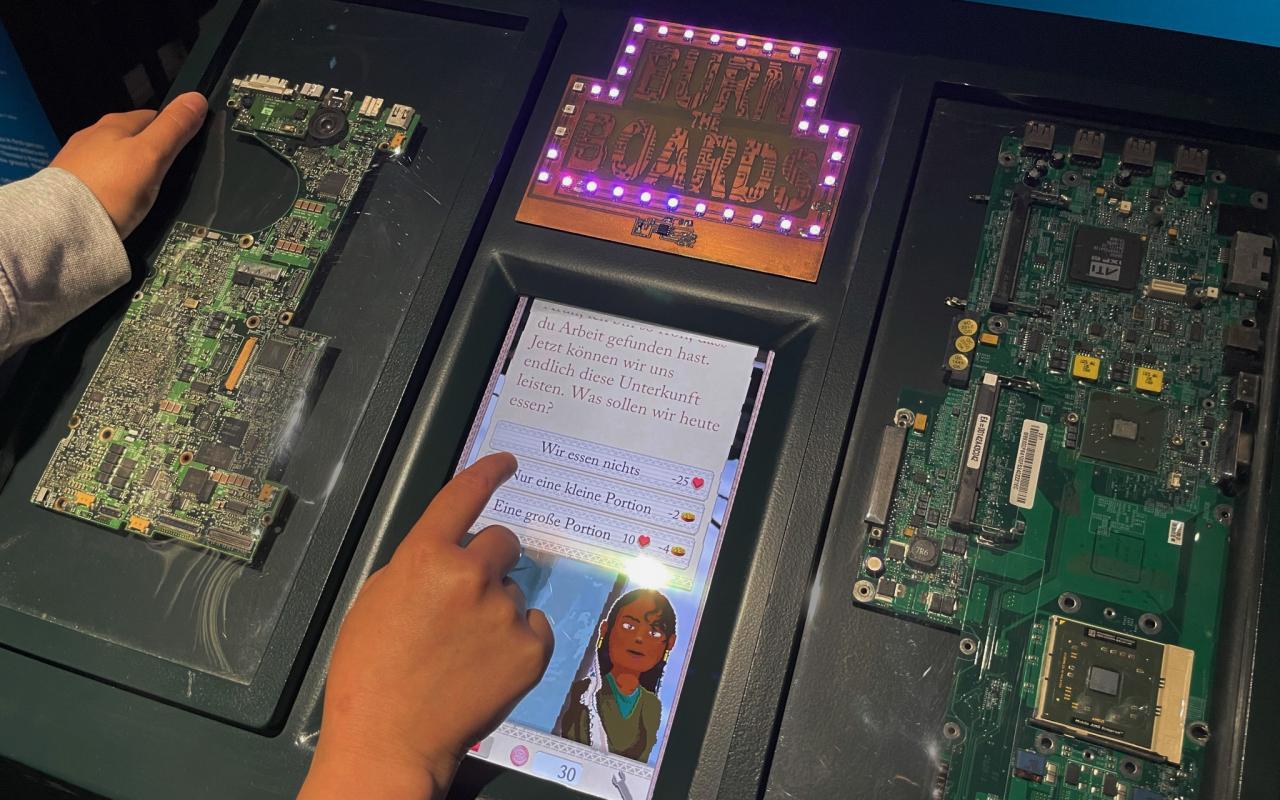 """Ausstellungsbild des Computerspiels """"Burn the Boards""""; Es erscheint folgender Text: """"Jetzt können wir uns endlich diese Unterkunft leisten. Was sollen wir heute essen?"""" Die Hand eines Spielenden ist dabei die Antwort """"Nur eine kleine Portion"""" zu wählen."""