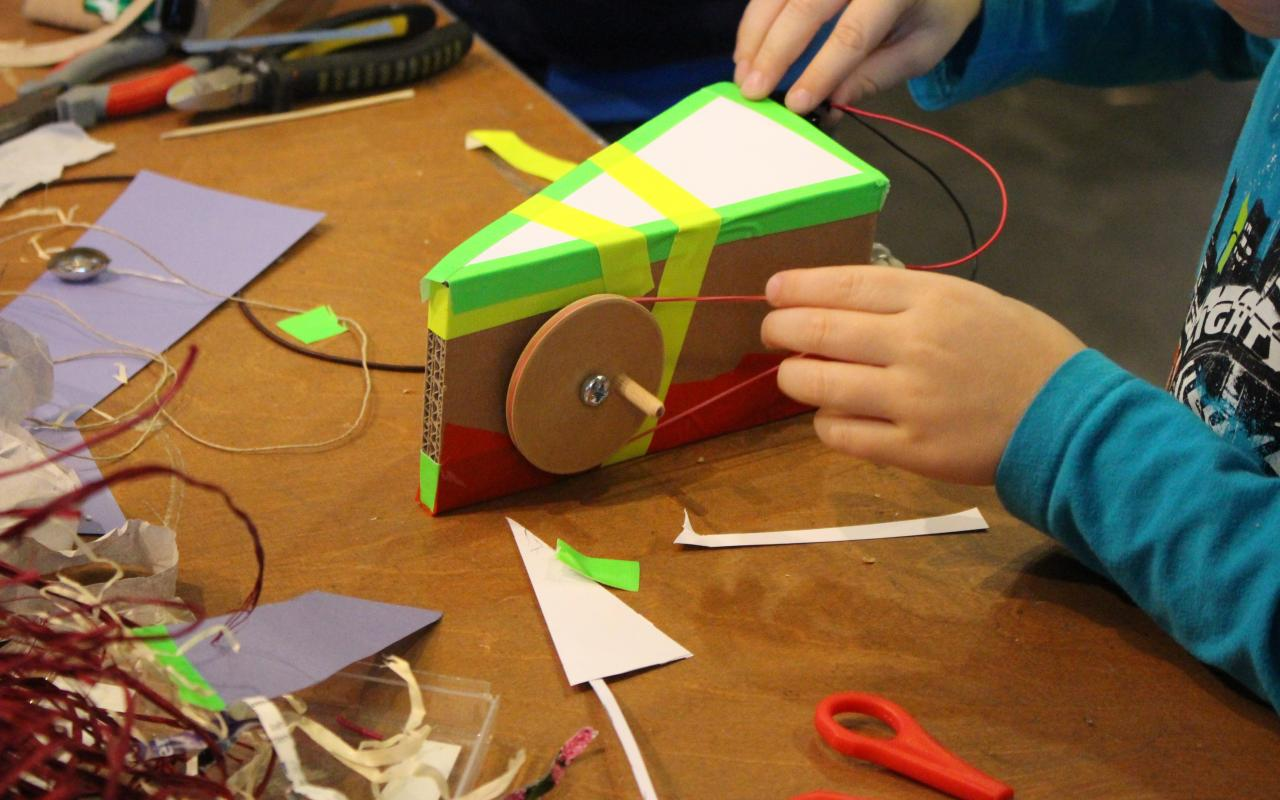 A kid works on a little automated construction, that it has equipped with a wheel, that is beeing rotated by a rubberband and a small motor.