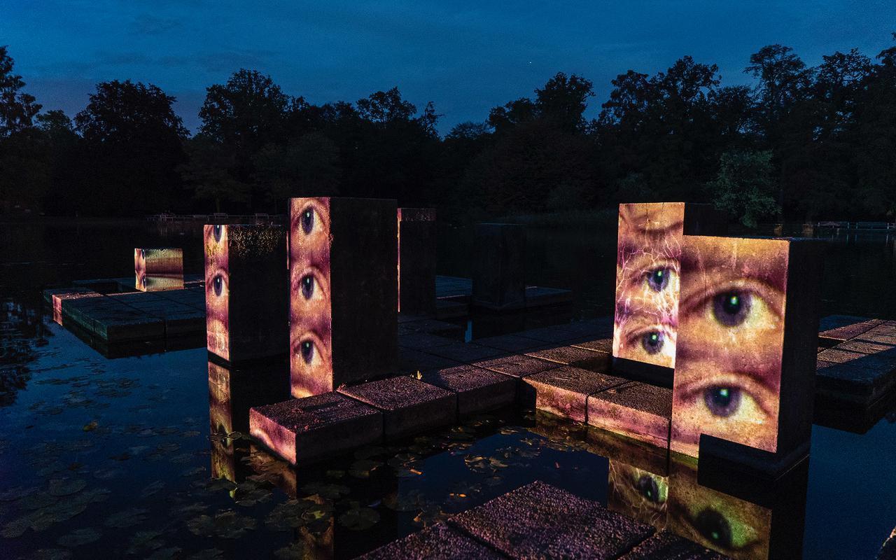 Wasserstelen in einem Park. Es ist später Abend. Auf die Stelen sind Augen gemappt, die offen in die Gegend blicken.