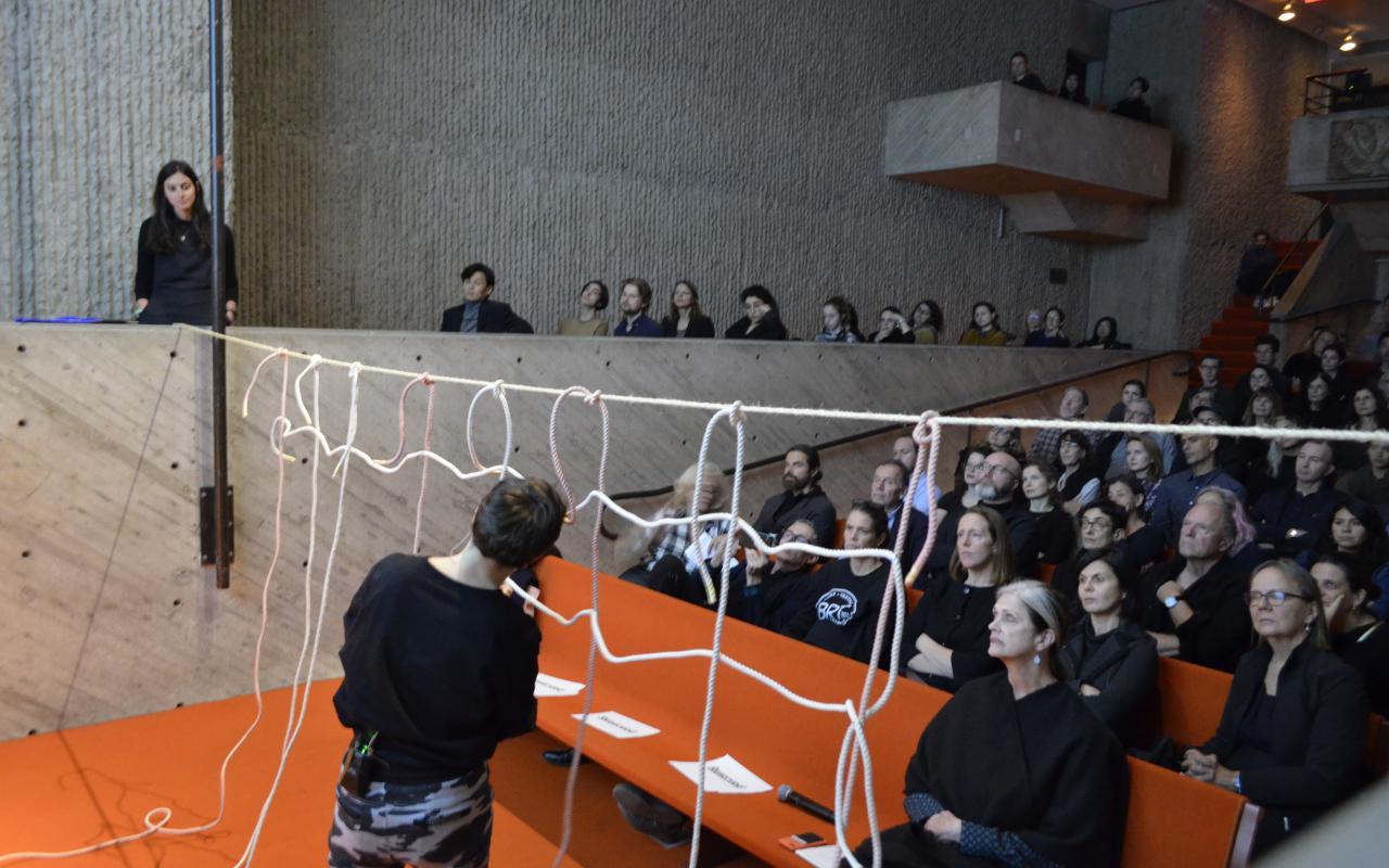 Foto eines gefüllten Vorlesungssaals. Die Künstlerin Judith Raum kreiert im Vordergrund ein Netz.