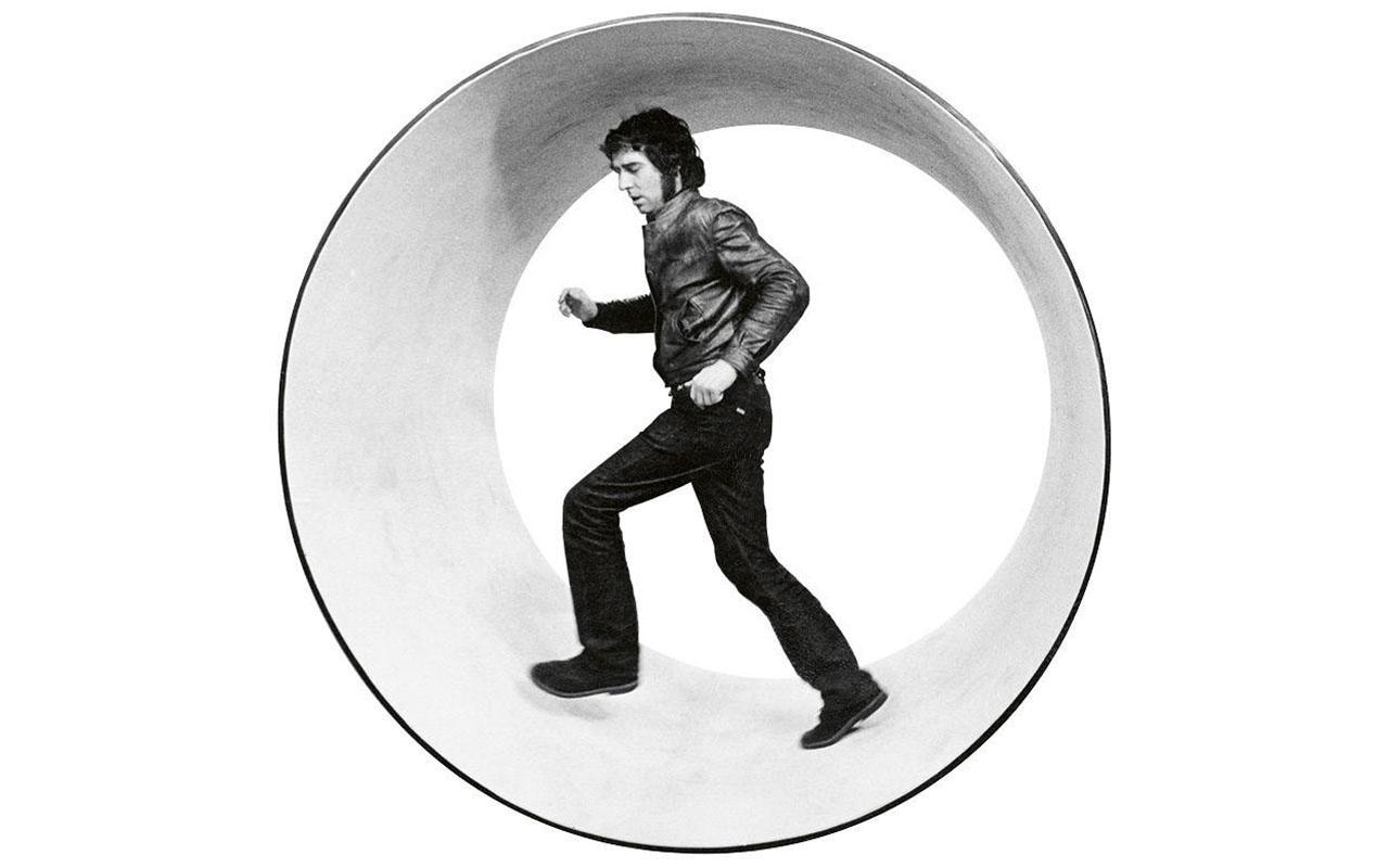 A man walks in a sliced barrel like a hamster in a hamster wheel.