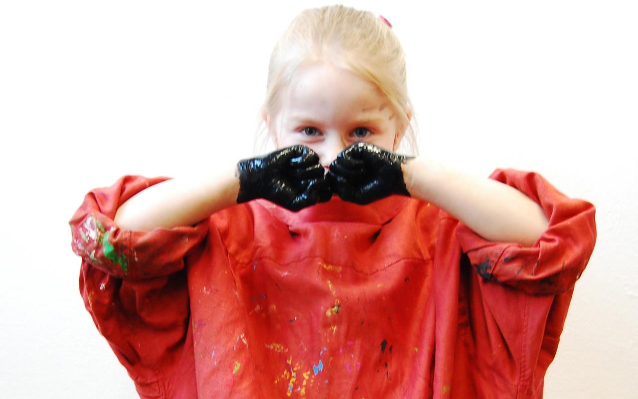 Ein junges Mädchen schaut direkt in die Kamera, dabei hält es die schwarzen Fäuste vor das Gesichtes. Das Mädchen trägt ein leuchtend rotes Hemd, das mit Farbe bekleckert ist.