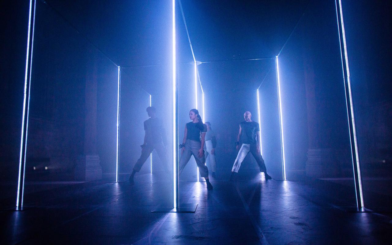 Eine Gruppe TänzerInnen steht in einem abgedunkelten Raum, der von blauen Neonröhren beleuchtet wird.