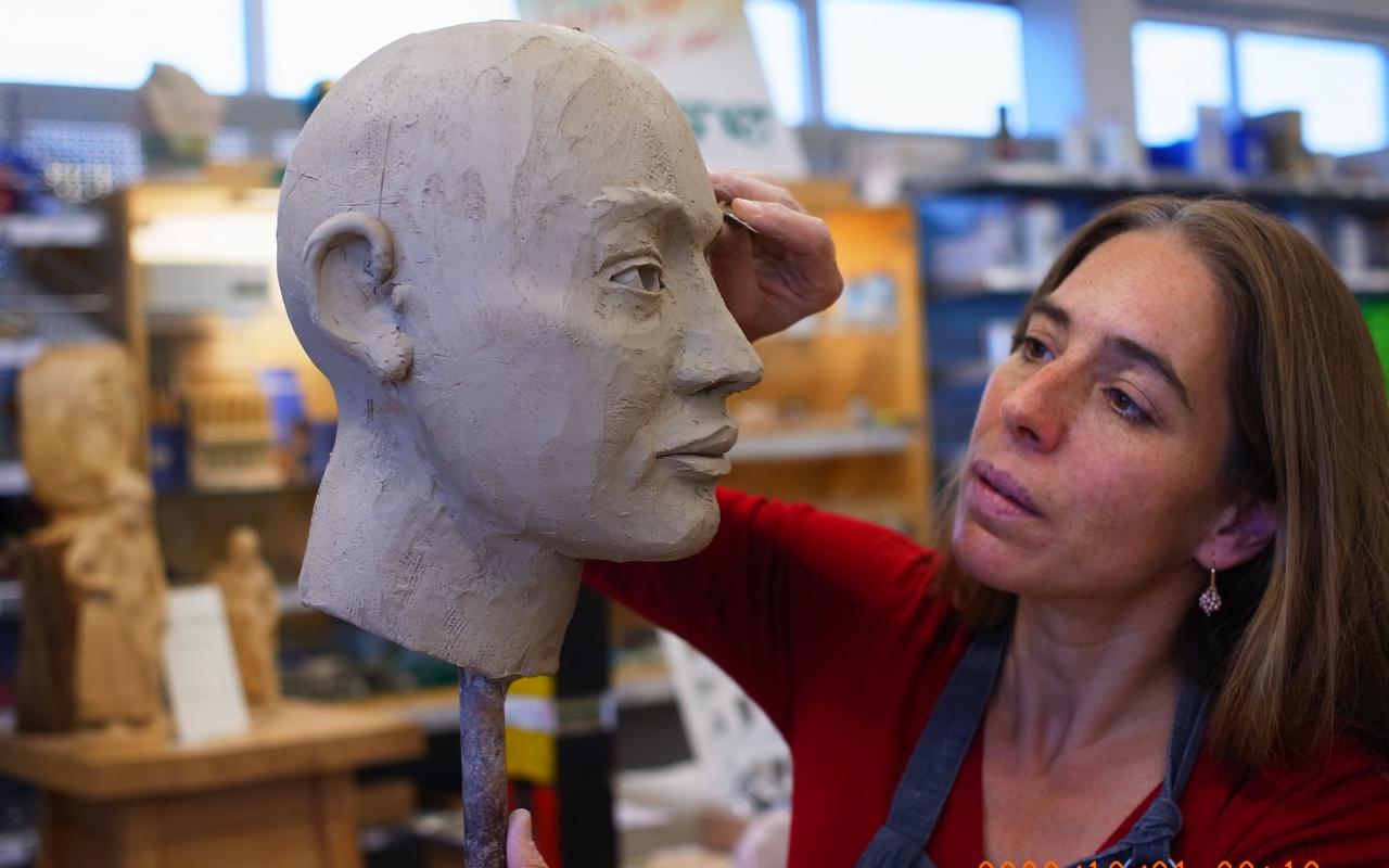 A model of a head sticking on a pole. A woman is working on it with a sculpting tool.