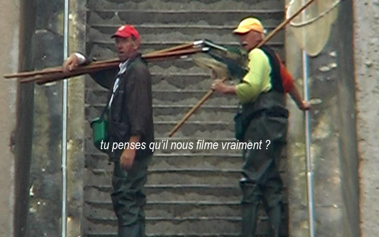 """Ein Filmstill aus dem Film Héros absurde von Edmund Kuppel zeigt zwei Mäner am Fuße einer Steintreppe im Freien, der eine links, der andere rechts auf der Treppe. Sie tragen Mützen und Fischereigerät. Sie fragen: """"Tu penses qu'il nous filment vraiment?"""""""