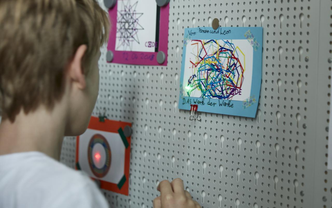 Ein Junge steht vor einer Wand mit Kinderzeichnungen.