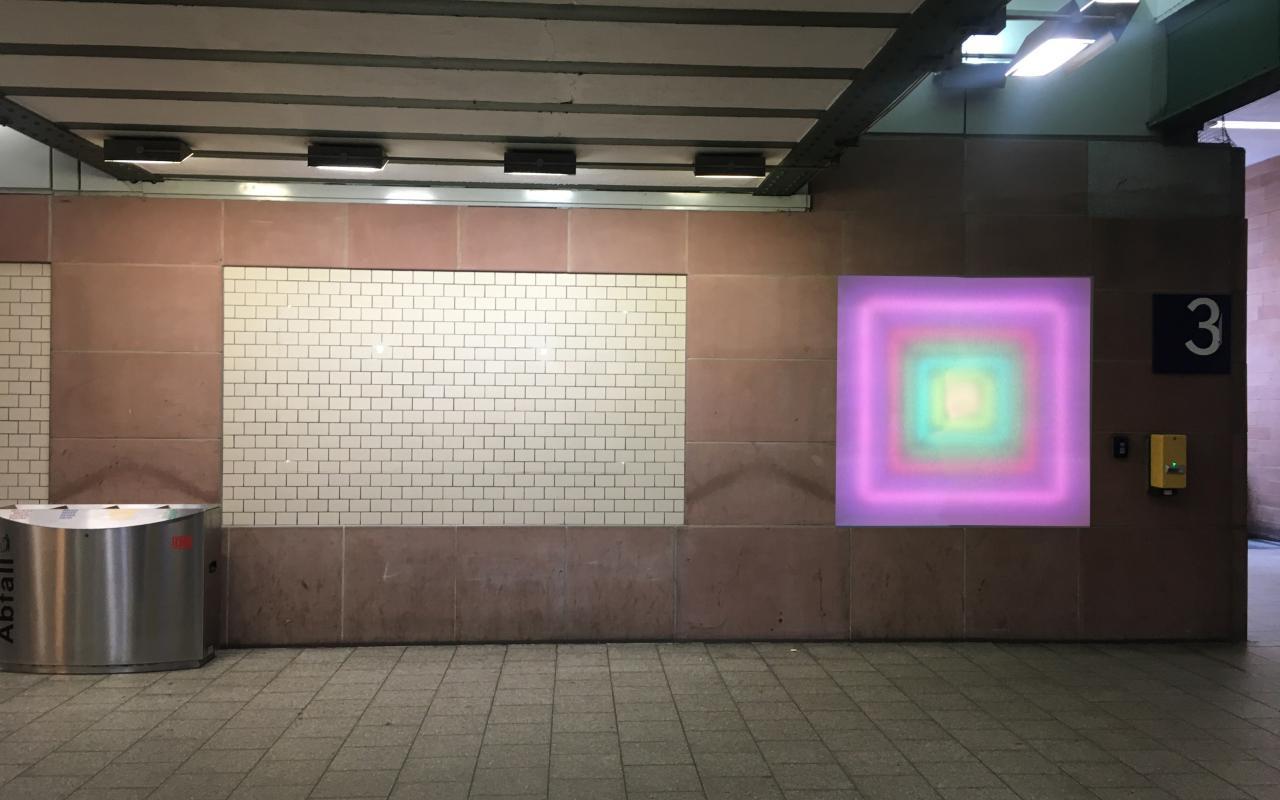 Zu sehen ist der Durchgang unter dem Karlsruher Hauptbahnhof. An der Wand ist ein leuchtendes Quadrat angebracht, das von innen nach außen einen Farbverlauf hat, der eine Tiefe erzeugt.