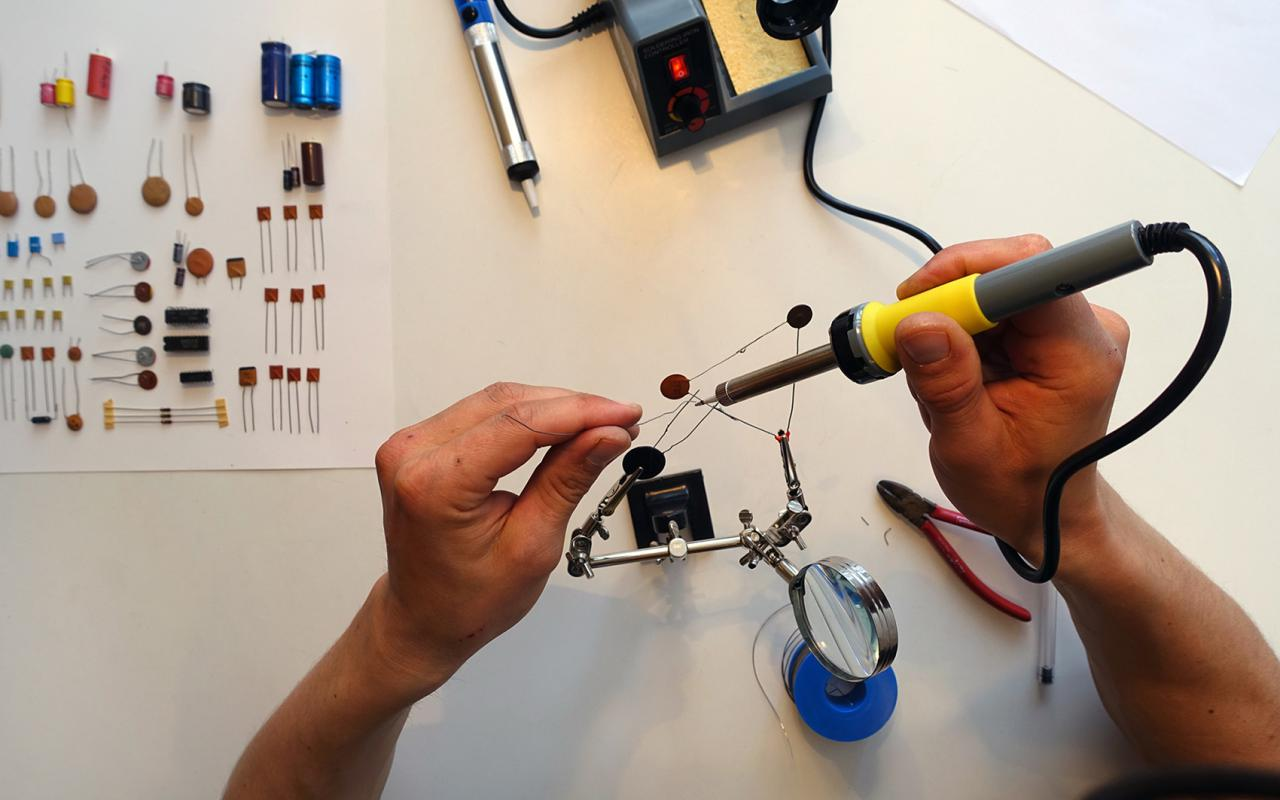 You can see hands from above that are holding a soldering iron. The person is soldering some wires together using a estra hand..