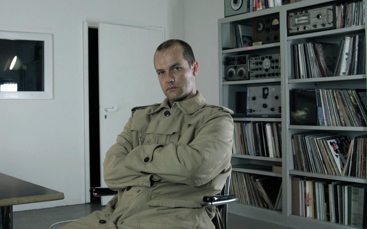 The scientist and componist Marcus Schmickler is sitting in front of a shelf filled with records and electric gadgets