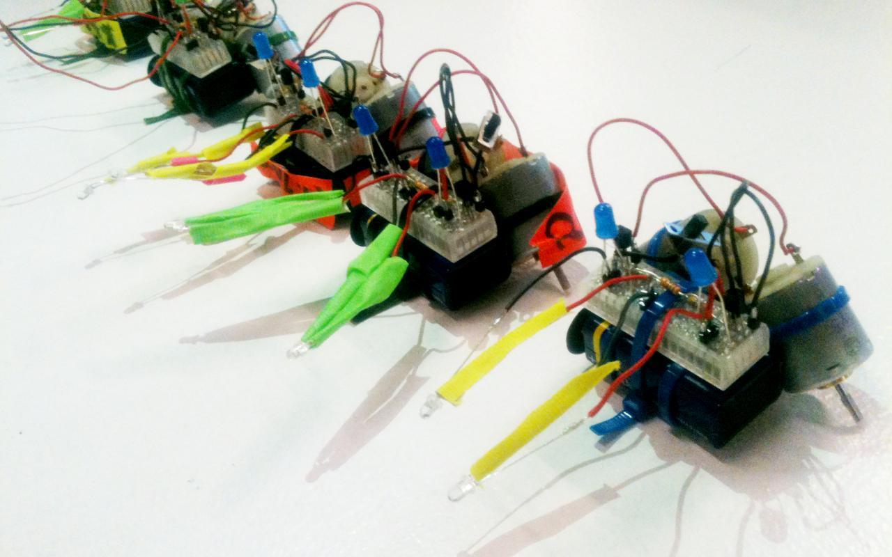 Fünf kleine T2-R2-Roboter aus verschienen elektronischen Teilen und durch Kabelbinder zusammengehalten.