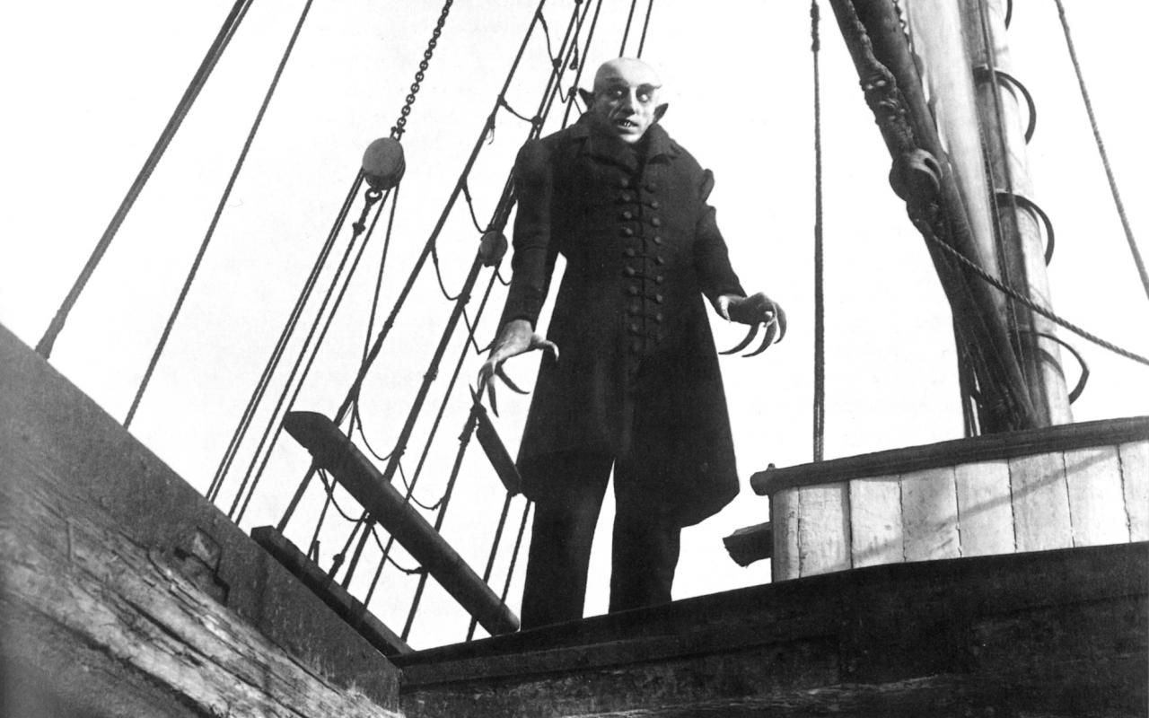 A man with claw hands is standing on a boat
