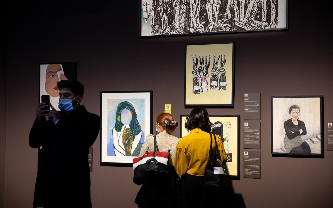 Zu sehen sind Besucher:innen, die sich von Überlebenden gemalte Kunstwerke sowie Porträtfotos anschauen