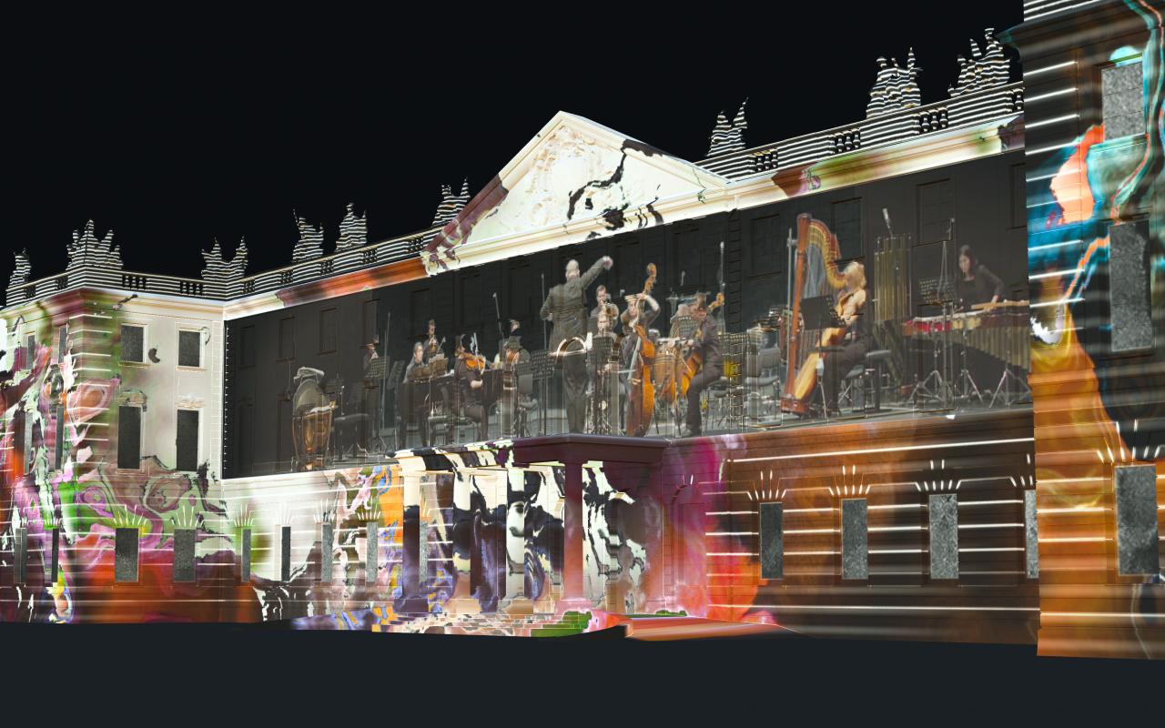 Auf der Karlsruher Schlossfassade ist ein Projection Mapping zu sehen, das in der Nacht leuchtet. Das Mapping zeigt bunte Farbwirbel, in deren Mitte ein Orchester spielt.