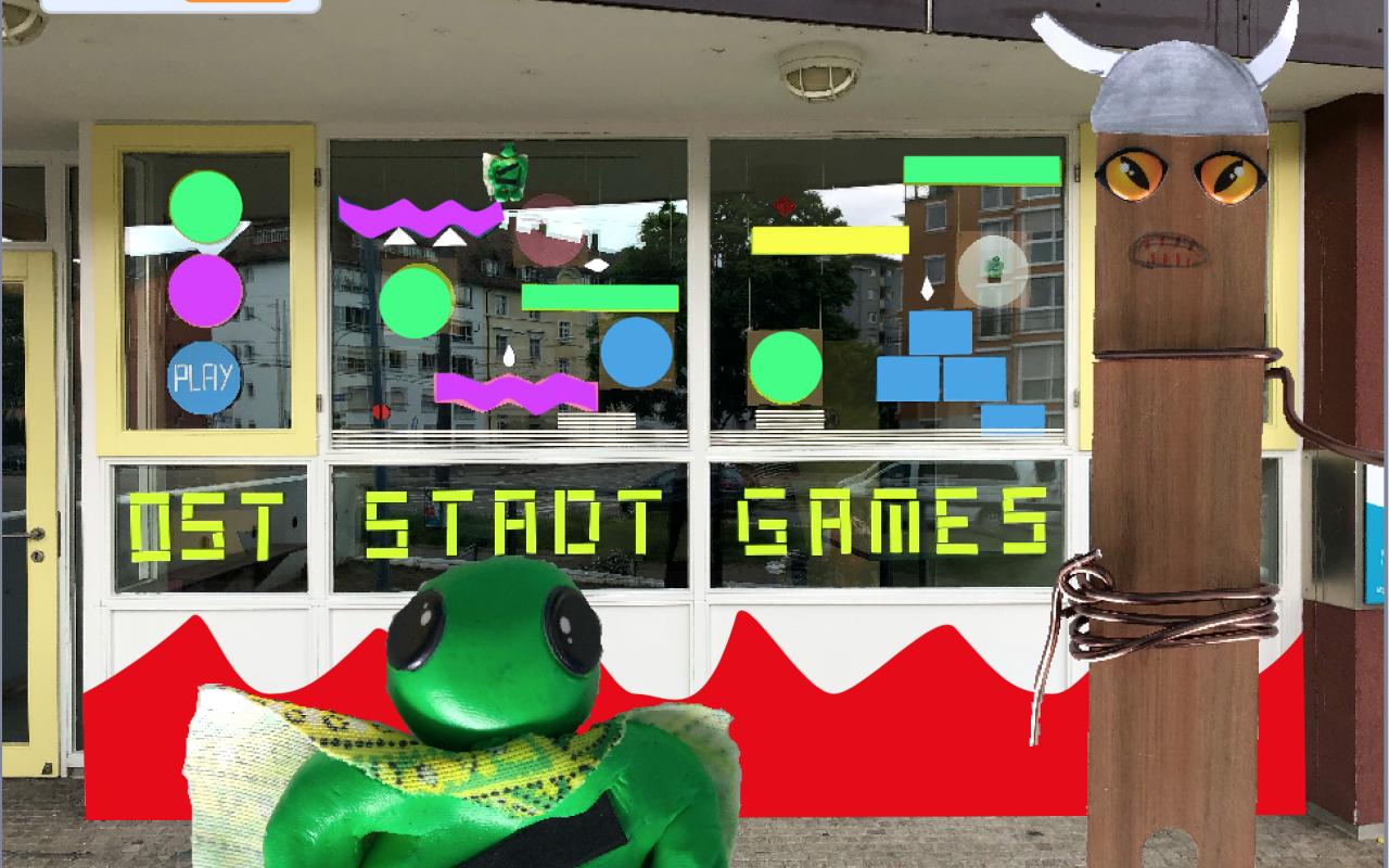 Außenansicht eines Fensters mit Basteleien und der Aufschrift »Oststadt Games«, im Vordergrund weitere Bastelarbeiten