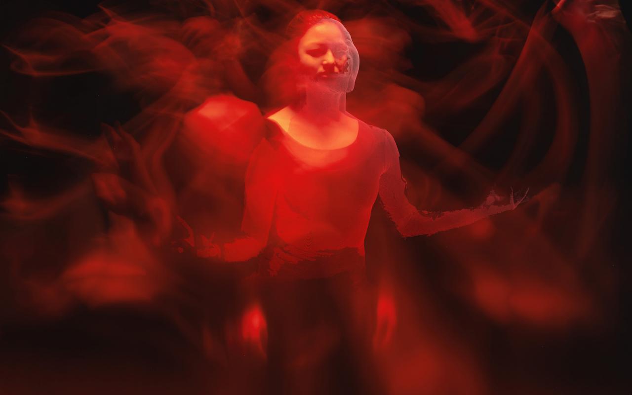 Das Foto zeigt eine von rotem Licht erleuchtete Frau in einem abgedunkelten Raum. In dieser Impression sieht man mehrere verschwommene Arme und Hände in Bewegung, die fast einer indischen Gottheit ähneln.
