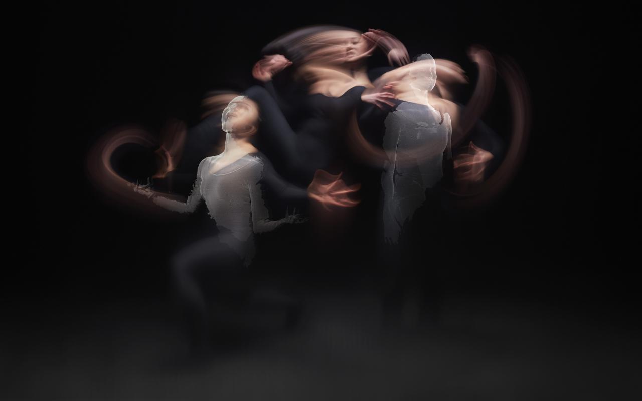 Drei Tänzerinnen werden in einem dunklen Raum angeleuchtet. Die Körper sind verschwommen und man weiß nicht so recht, ob es eine Person oder drei sind. Zum Teil ist ragen aus ihren Körpern computeranimierte Versionen Haut.