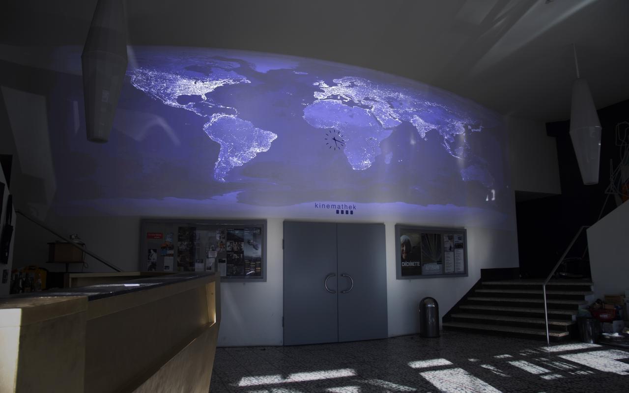 Zu sehen ist ein Wand mit einer großen Tür. Über der Tür ist eine Weltkarte in kalten Farben auf die Wand projiziert.