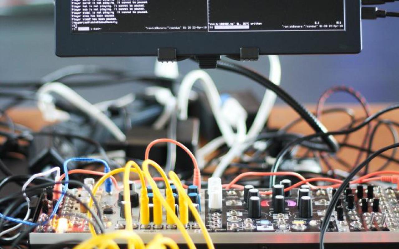 Auf einem Display ist Code zu sehen. Darunter steht ein Mischpult mit bunten Kabel auf einem Tisch.