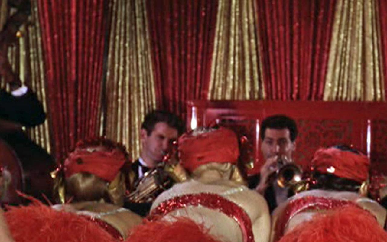 Two trumpet players are seen in front of a golden and red curtain. In the audience sit three women with red headdresses