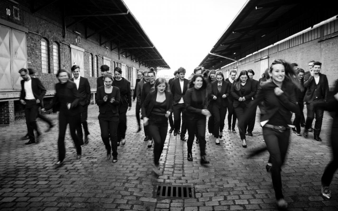 The black-and-white picture shows the members of the Ensemble Reflektor running across a paved street.