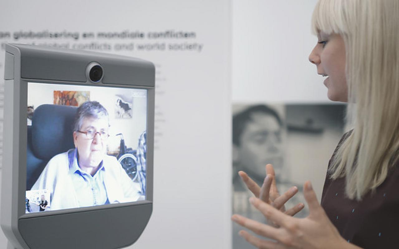 Das Bild zeigt einen Führungsroboter im VanAbbe Museum und eine Museumsführerin.