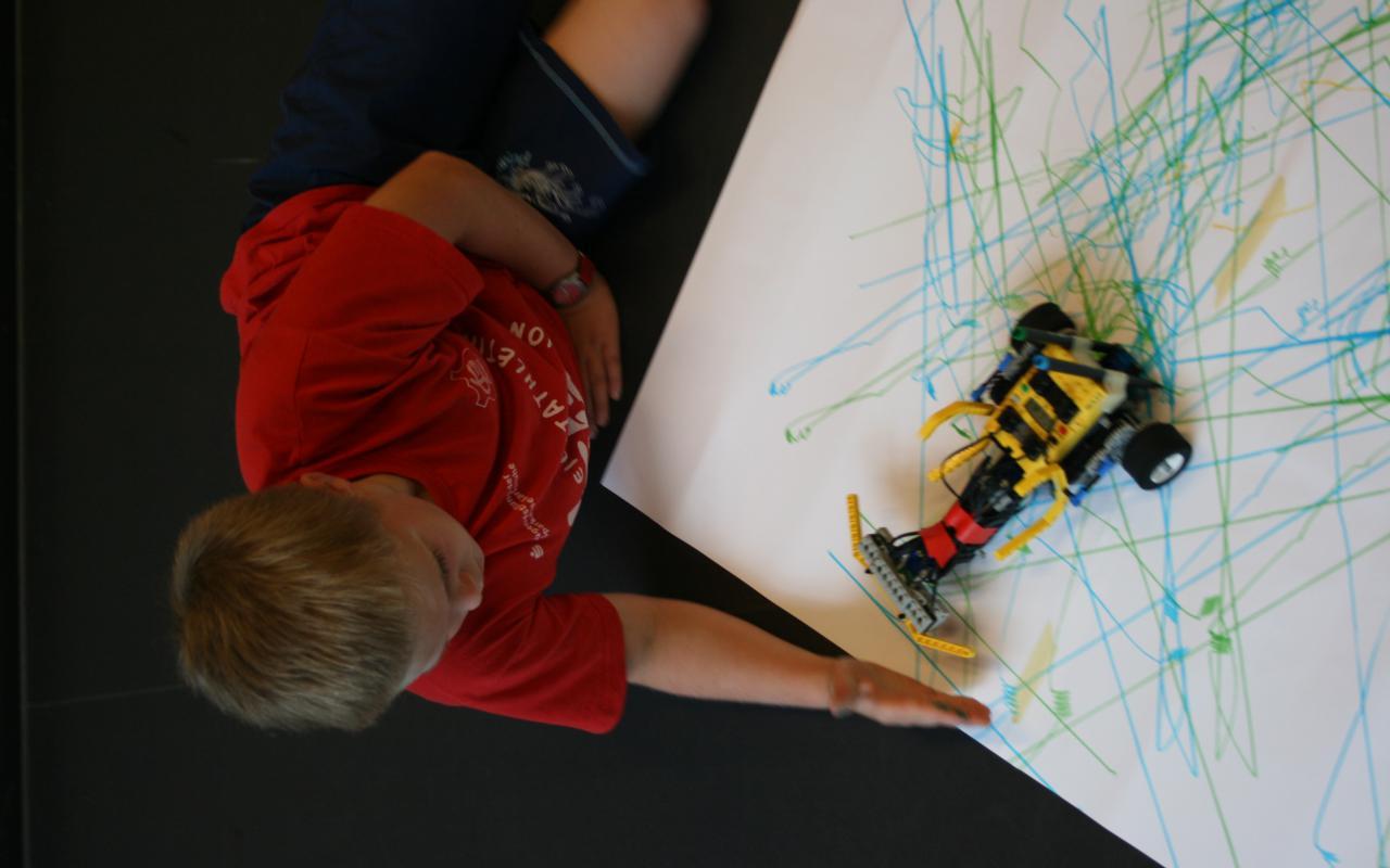 Ein mit Sensoren ausgestatteter Lego-Roboter erkennt als Hindernis die Hand eines Kindes, der sie vor den Roboter hält.