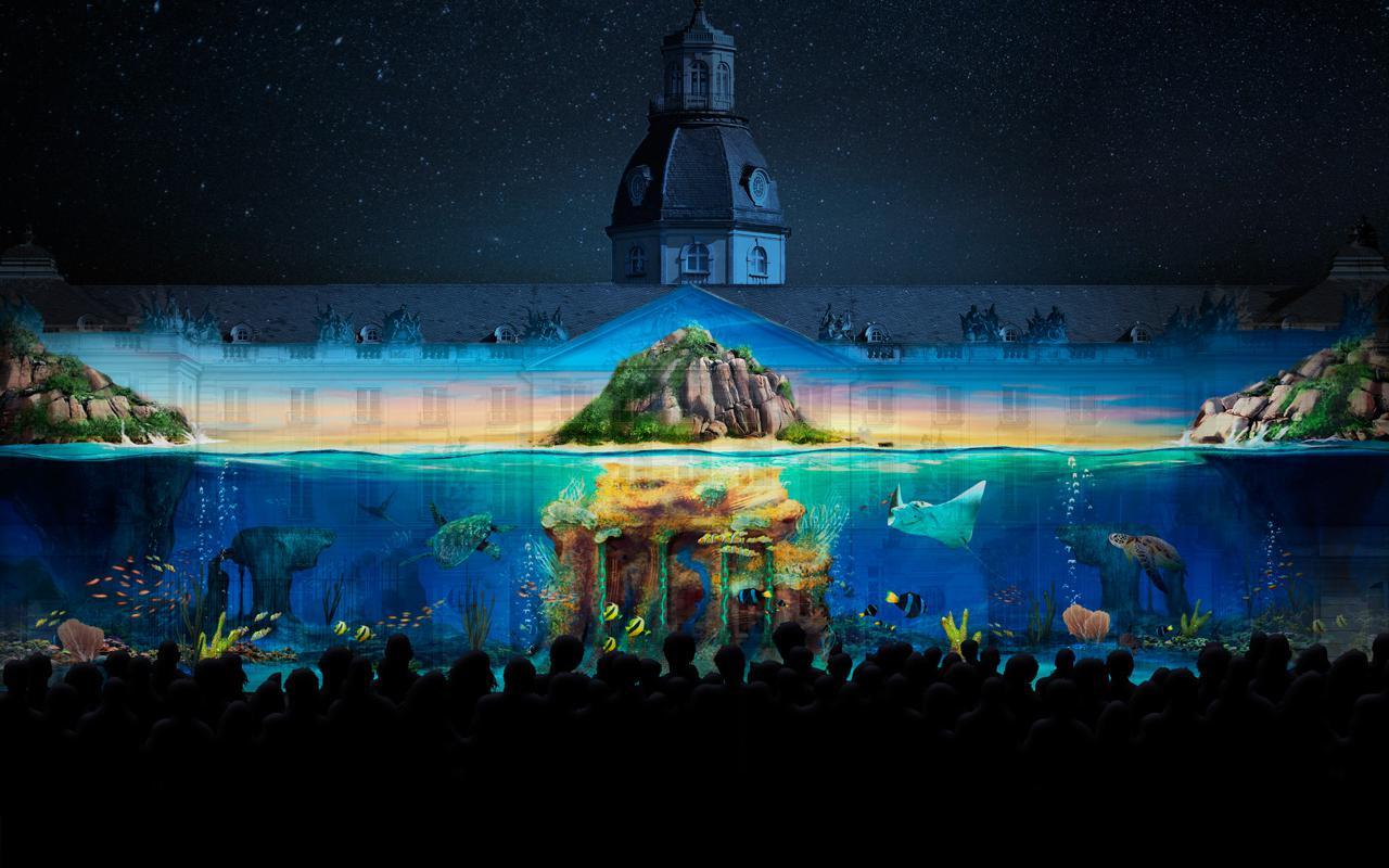 Das Foto zeigt ein Projection Mapping der Gruppe Maxin10sity auf dem Karlsruher Schloss. Zu sehen ist eine mystische Unterwasserwelt.