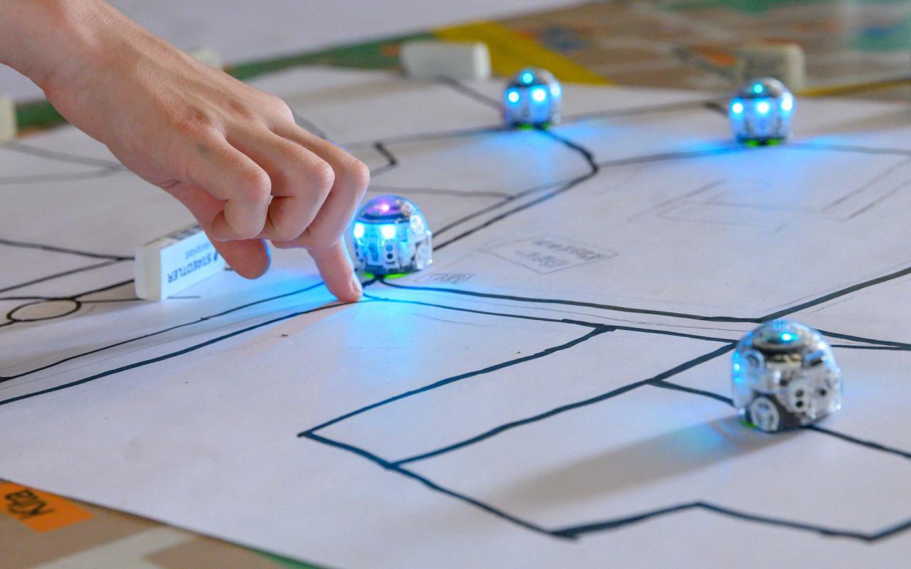 Auf dem Foto: Kleine, blau leuchtende Roboter fahren schwarzen Linien auf einem Blatt Papier entlang