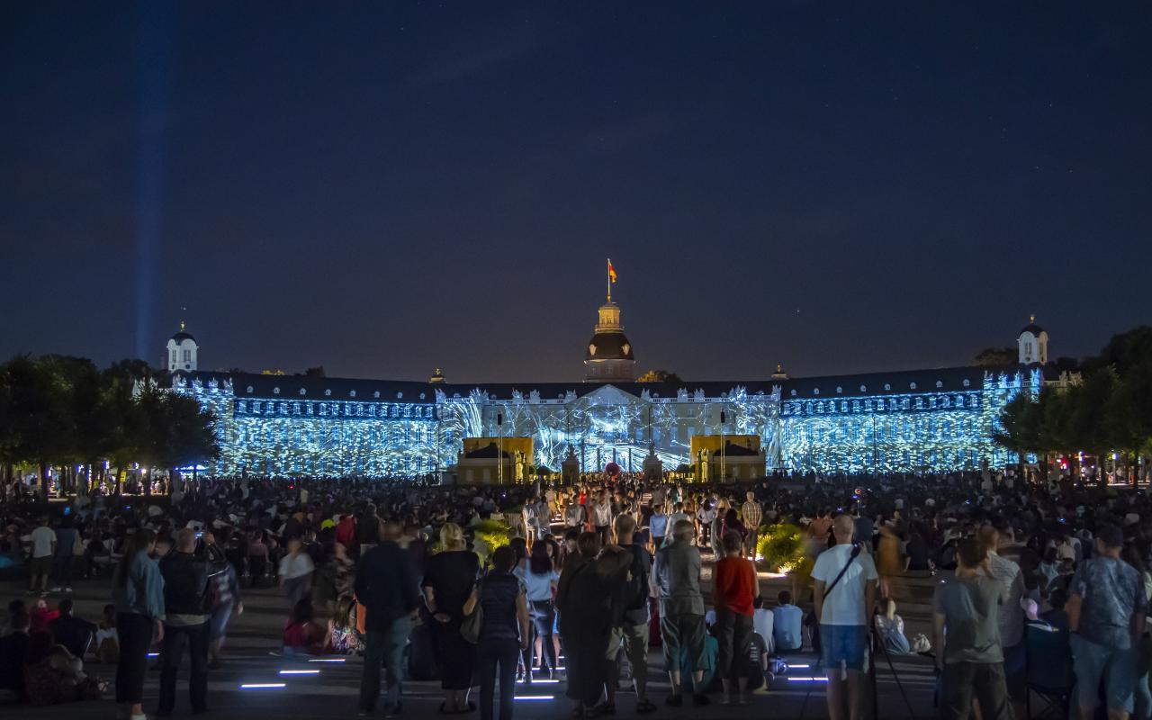 Das Foto zeigt die Arbeit »MEMORIES« projeziert auf dem Karlsruhe Schloss am Eröffnungsabend der Schlosslichtspiele Karlsruhe 2018