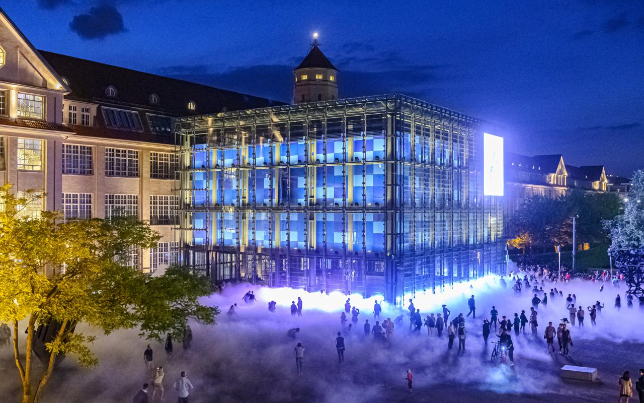 The photo was taken at night with a drone. It shows the fog sculpture and many silhouettes of visitors of KAMUNA 2019. The cube and the facade of the building are brightly illuminated.
