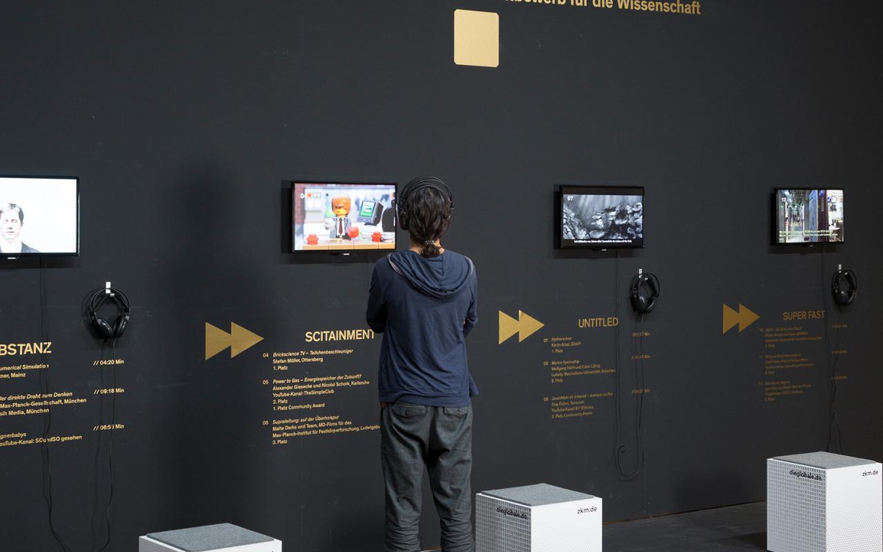Ausstellungsansicht von »Fast Forward Science«: Eine Wand mit Monitoren, davor ein junger Mann.